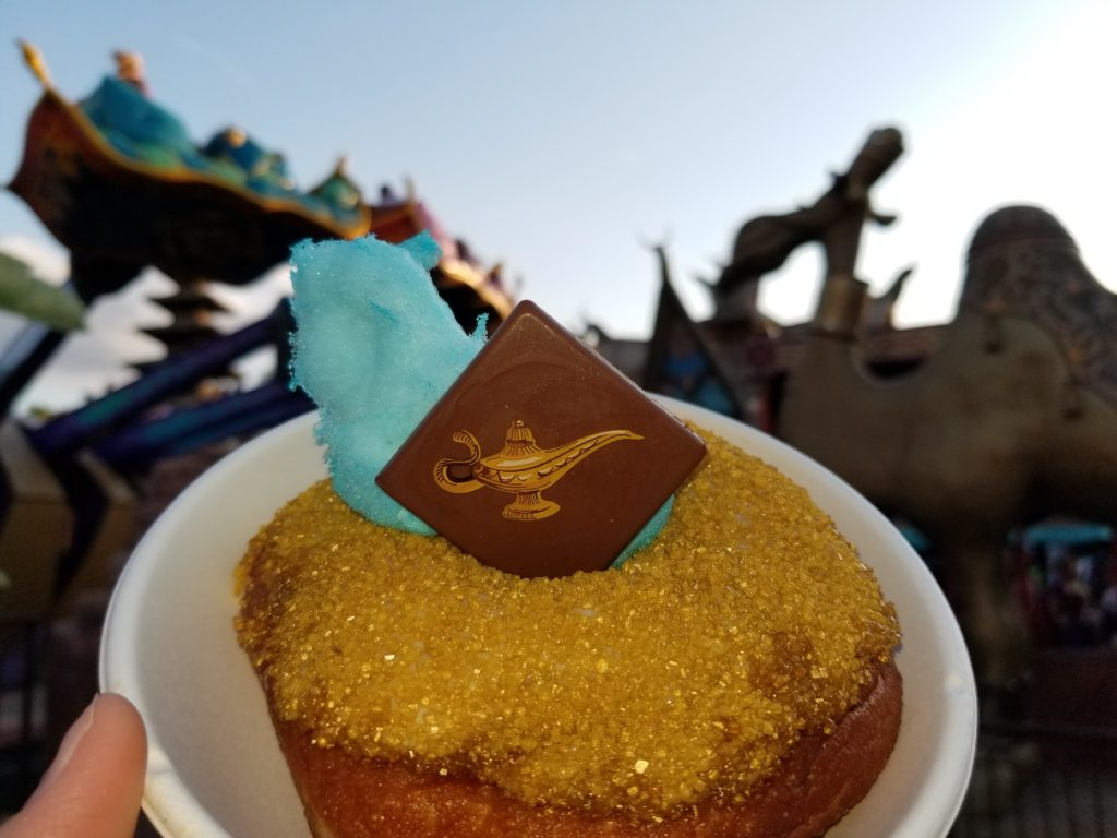 "The ""Wish Granted Donut"" in front of the camel and ""The Magic Carpets of Aladdin"" ride."