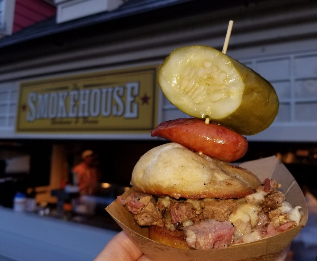 Beef Brisket Burnt Ends and Smoked Pork Belly Slider with Garlic Sausage, Chorizo, Cheddar Fondue and House-made Pickle in front of the Smokehouse: Barbecue and Brews at the American Adventure