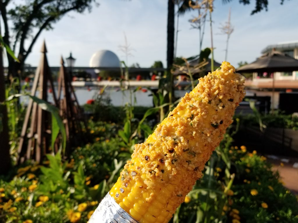 Grilled Street Corn on the Cob with Savory Garlic Spread in front of corn stalks and Spaceship Earth