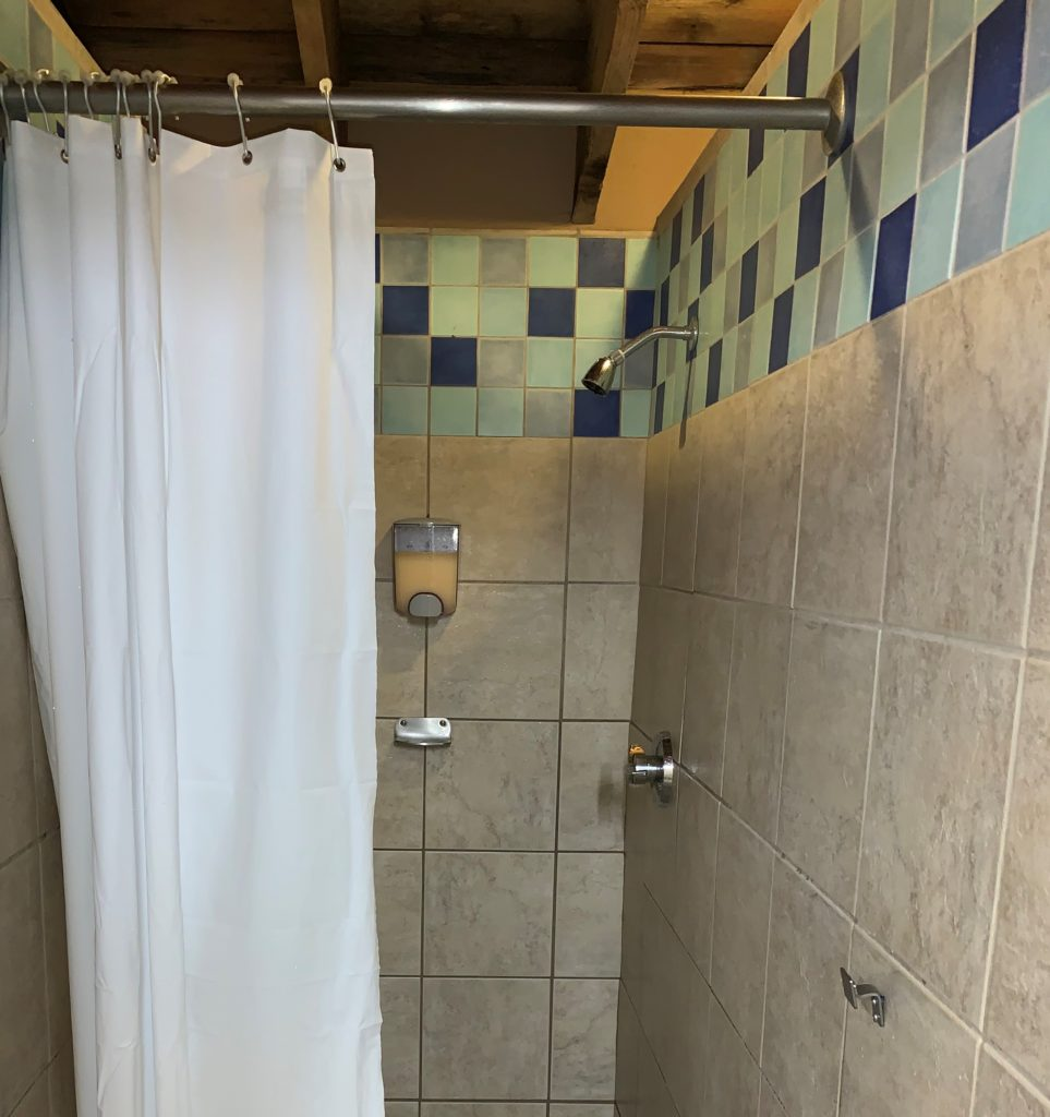 Image of a shower stall at Disney's Blizzard Beach water park with only one hook on the wall.